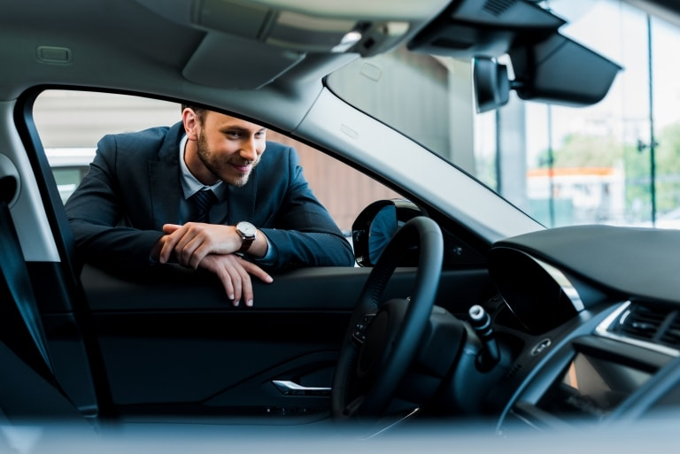 Man happy with car and steering wheel