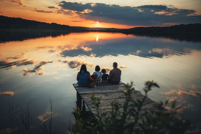 family sits on the shore of a large lake at sunset
